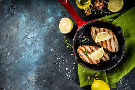 Foto de Grilled tuna fish steaks with lemon and spices on frying pan, dark blue concrete background copy space top view - Imagen libre de derechos