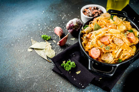 Photo for German, polish, Austrian cuisine dish, Bigos - sauerkraut cabbage stewed with meat, mushrooms and sausages, in small pan on dark concrete background.Top view with copy space. - Royalty Free Image