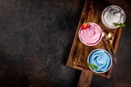 Foto de Healthy diet summer dessert, vanilla and berry frozen yogurt or  soft ice cream in white bowls, white marble background copy space above - Imagen libre de derechos