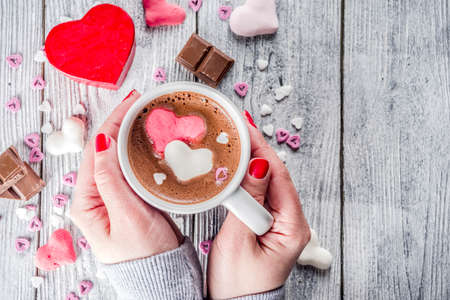 Foto de Girl hands hold hot chocolate with marshmallow hearts, red pink white color with chocolate pieces, sugar sprinkles, old wooden background copy space top view, hands in pictute flatlay - Imagen libre de derechos