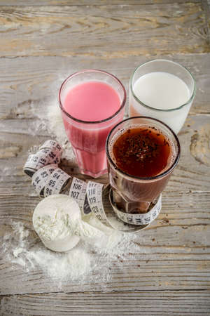 Foto de Healthy organic diet drink. Chocolate, berry and vanilla protein shakes. Non dairy protein vegan cocktails. With measuring tape. Concept of weight loss, fitness, healthy lifestyle. - Imagen libre de derechos