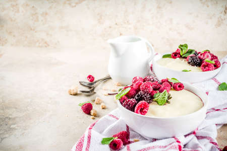 Photo for Two bowl with Semolina porridge with fresh berries, beige stone table copy space top view - Royalty Free Image