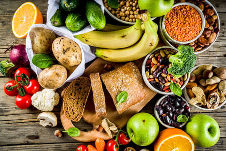 Foto de Healthy food. Selection of good carbohydrate sources, high fiber rich food. Low glycemic index diet. Fresh vegetables, fruits, cereals, legumes, nuts, greens. Wooden background copy space - Imagen libre de derechos
