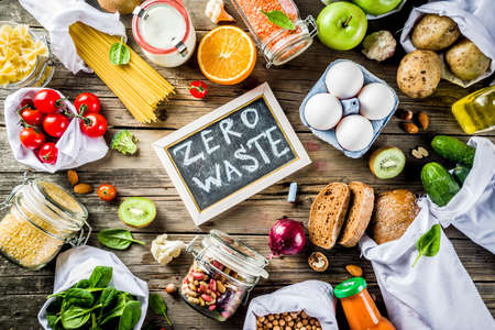Foto de Zero waste shopping and sustanable lifestyle concept, various farm organic vegetables, grains, pasta, eggs and fruits in reusable packaging supermarket bags. copy space top view, wooden background - Imagen libre de derechos