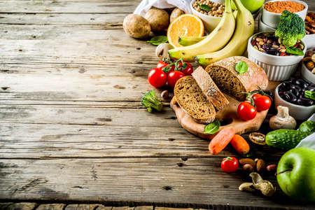 Foto de Healthy food. Selection of good carbohydrate sources, high fiber rich food. Low glycemic index diet. Fresh vegetables, fruits, cereals, legumes, nuts, greens. Wooden background copy space - Imagen libre de derechos
