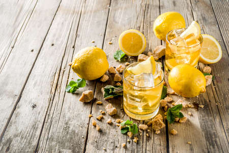 Foto de Lemonade or iced summer tea, with fresh lemon slices, sugar and mint leaf, rustic wooden table, copy space - Imagen libre de derechos