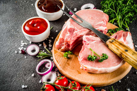 Photo pour Raw meat, pork steaks, ready for cooking, with herbs, black concrete background copy space - image libre de droit