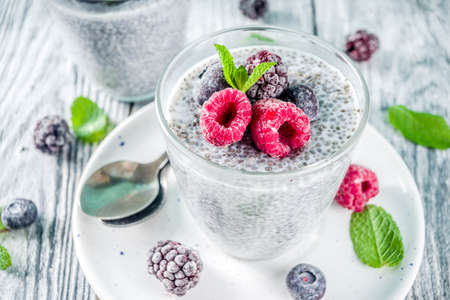 Photo for Summer healthy breakfast dessert in glass, overnight vegan chia pudding with non-dairy milk, frozen raspberry, blackberry and blueberry, on light blue and wooden background copy space - Royalty Free Image