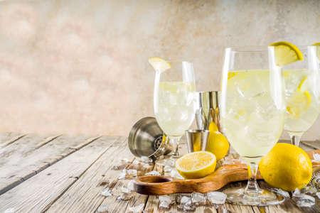 Foto de Trendy summer cold drink. St Germain French Spritz cocktail with lemon slices, old rustic wooden background copy space - Imagen libre de derechos