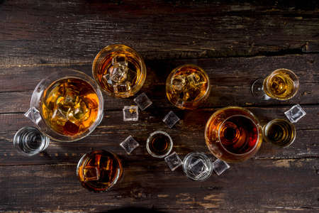 Photo for Assortment various hard and strong alcoholic drinks in different glasses: vodka, cognac, tequila, brandy and whiskey, grappa, liqueur, vermouth, tincture, rum, etc. Wooden background copy space - Royalty Free Image