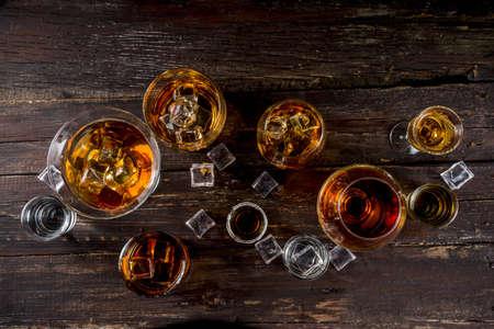 Foto de Assortment various hard and strong alcoholic drinks in different glasses: vodka, cognac, tequila, brandy and whiskey, grappa, liqueur, vermouth, tincture, rum, etc. Wooden background copy space - Imagen libre de derechos