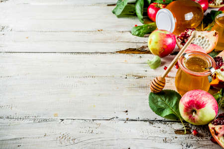 Photo pour Jewish Autumn Rosh Hashana celebration. Traditional products for the celebration of Rosh Hashanah - apples with leaves, pomegranate, honey, honeycombs, white wooden  background - image libre de droit