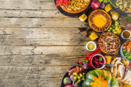 Foto de Thanksgiving family dinner setting concept. Traditional Thanksgiving day food  with turkey, green beans and mashed potatoes, stuffing, pumpkin, apple and pecan pies, rustic wooden table - Imagen libre de derechos