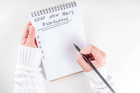 Photo pour Woman hands ready to write list of her 2020 new year goals in notepad, top view flatlay copy space white background - image libre de droit