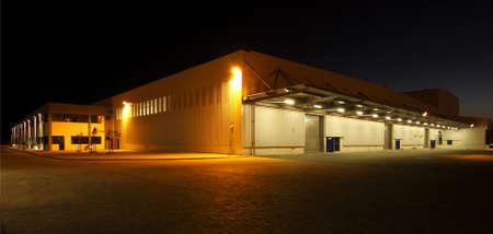 Foto de wide angle view of a modern warehouse at night in flood light light - Imagen libre de derechos