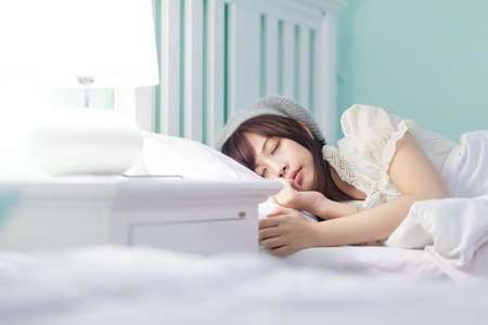 Photo pour Charming Asian girl wearing pajamas on the bed - image libre de droit