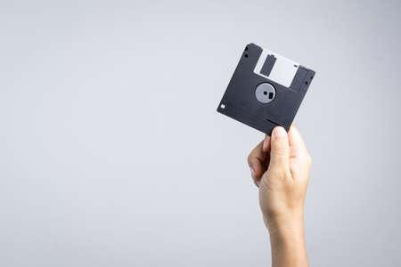 Foto de Hand holding floppy disk on white background - Imagen libre de derechos