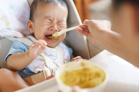 Photo pour 6 months old Asian baby refuse to eat food and crying over feeding time, - image libre de droit