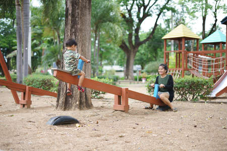 Photo pour Asian boy about 2 year and 3 months in military suit playing seesaw and having fun with his mother at kid training playground for muscle development - image libre de droit