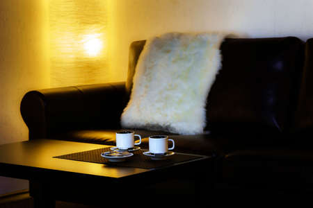 Two cups of coffee on the table in semi-dark comfort room