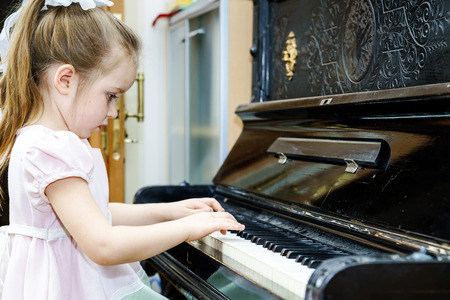 Foto de Cute little girl playing old piano at home lesson - Imagen libre de derechos