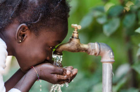 Foto de Clean Freshwater Scarcity Symbol: Black Girl Drinking from Tap. Young African girl drinking clean water from a tap. Hands with water pouring from a tap in the streets of the city Bamako, Mali. - Imagen libre de derechos