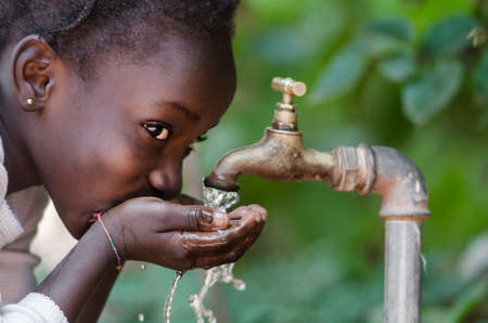 Foto de Beautiful African Child Drinking from a Tap (Water Scarcity Symbol). Young African girl drinking clean water from a tap. Water pouring from a tap in the streets of the African city Bamako, Mali. - Imagen libre de derechos