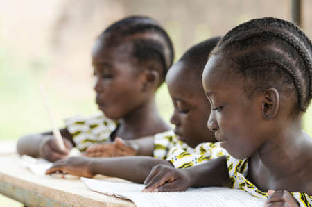 Photo pour Two beautiful African girls and one African boy reading and writing at school as an educational symbol outside their school in Bamako, Mali. Beautiful education symbol background. - image libre de droit