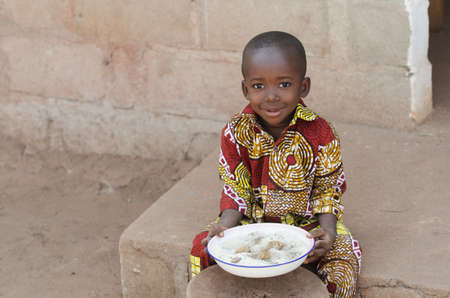 Photo for Candid Shot of Little Black African Boy Eating Rice Outdoors - Royalty Free Image