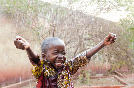 Foto de Water is coming! African ethnicity little boy happy to finally get some rain - Imagen libre de derechos
