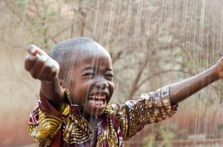 Foto de Little Native African Boy Standing Outdoors Under the Rain - Imagen libre de derechos