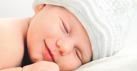 Photo pour smiling european newborn baby in white hat - image libre de droit