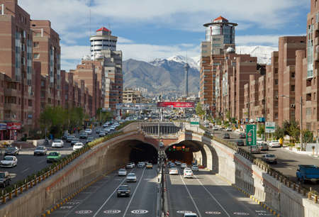 Cars Passing Through Tohid Tunnel of Tehran with Milad Tower and Alborz Mountains in the Background.