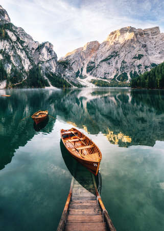 Photo pour Boats and slip construction in Braies lake with crystal water in background of Seekofel mountain in Dolomites in morning, Italy Pragser Wildsee - image libre de droit