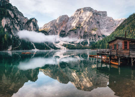 Photo pour Panoramic view of Braies Lake with the hut and boats in Dolomites mountains and Seekofel in the morning, Pragser Wildsee, South Tirol, Italy - image libre de droit