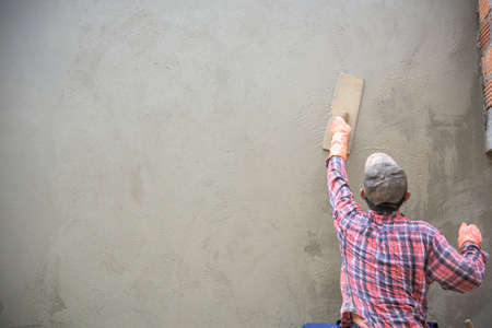 Photo pour Builder worker plastering  concrete at wall - image libre de droit