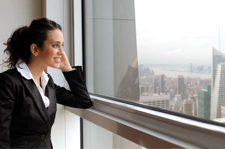 Smiling businesswoman looking out of a window