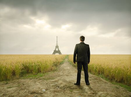 Businessman on a wheatfield with Eiffel Tower on the background