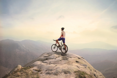 Cyclist on a peak in the mountains