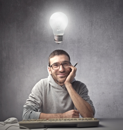 Photo pour Smiling young man in front of a computer with light bulb over his head - image libre de droit