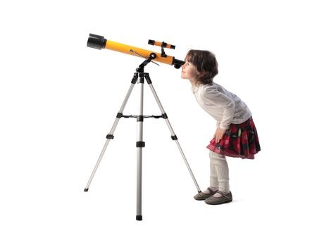 Foto de Little girl looking into a telescope - Imagen libre de derechos