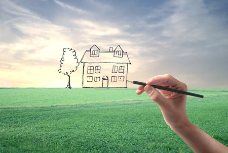 Hand drawing a house in a large grace field