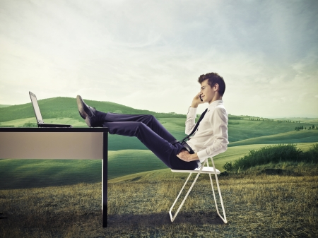 Foto de Young businessman, on a hill, make a call with feet on desk - Imagen libre de derechos