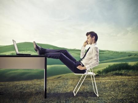Photo pour Young businessman, on a hill, make a call with feet on desk - image libre de droit