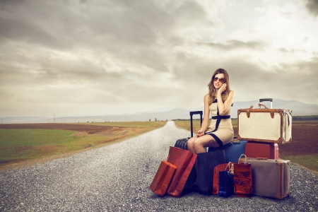 Photo pour Fashion woman with lots of suitcases in the middle of the street - image libre de droit