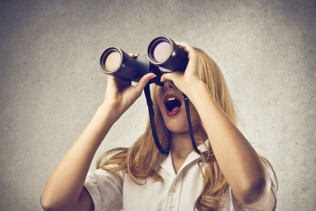 Photo for astonished woman looking at something with a binoculars - Royalty Free Image