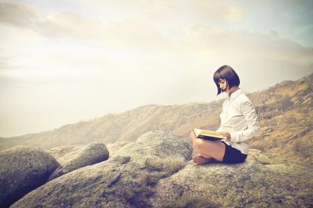 Foto de woman reading on a rock - Imagen libre de derechos