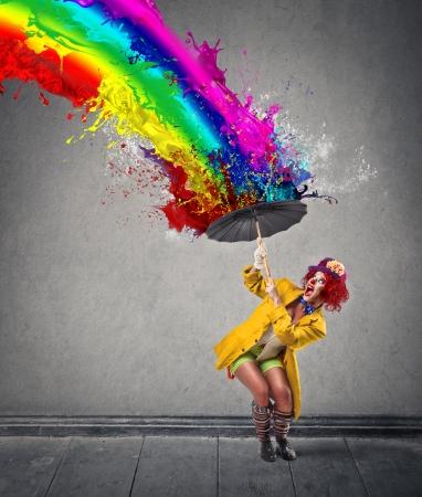 Foto de clown protecting herself from a paint-rainbow - Imagen libre de derechos