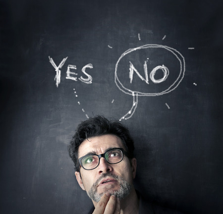 Photo pour man with yes or no on black board - image libre de droit