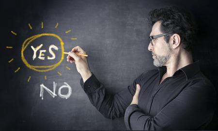 Photo pour man with yes or no on a black board - image libre de droit